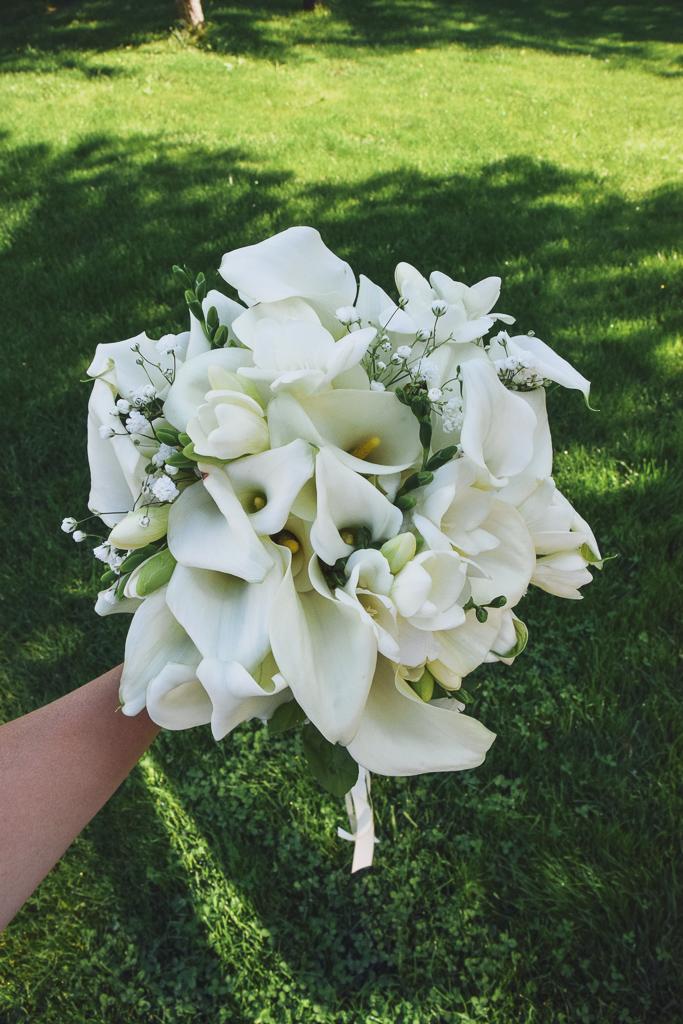 Buchet de mireasă cu cale albe, frezii, floarea miresei și un fir de busuioc de noroc
